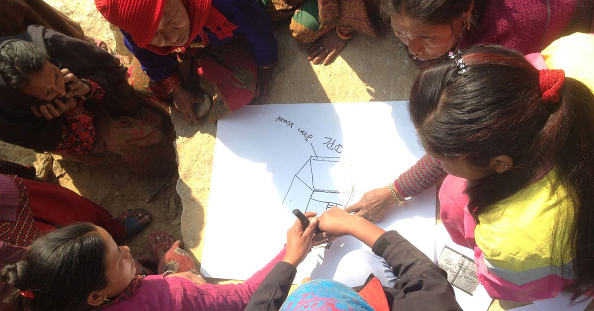 Women huddle around paper to draw house design