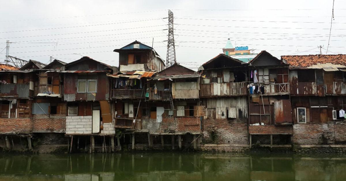Precarious houses along polluted riverbank