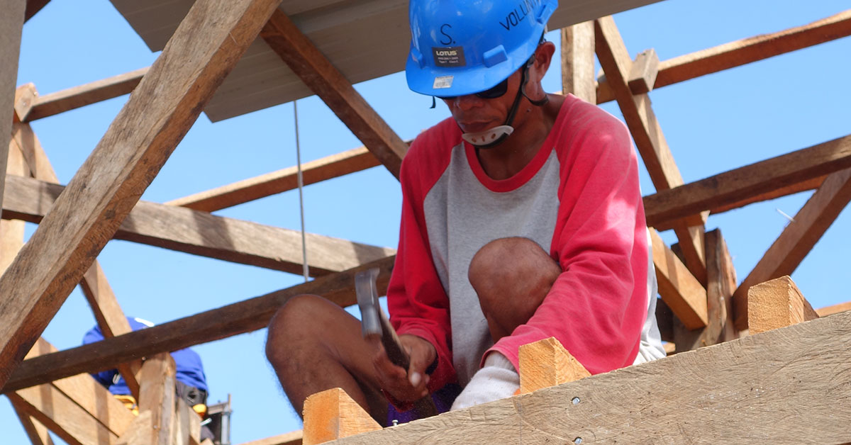 Construction worker nailing flooring on timber house
