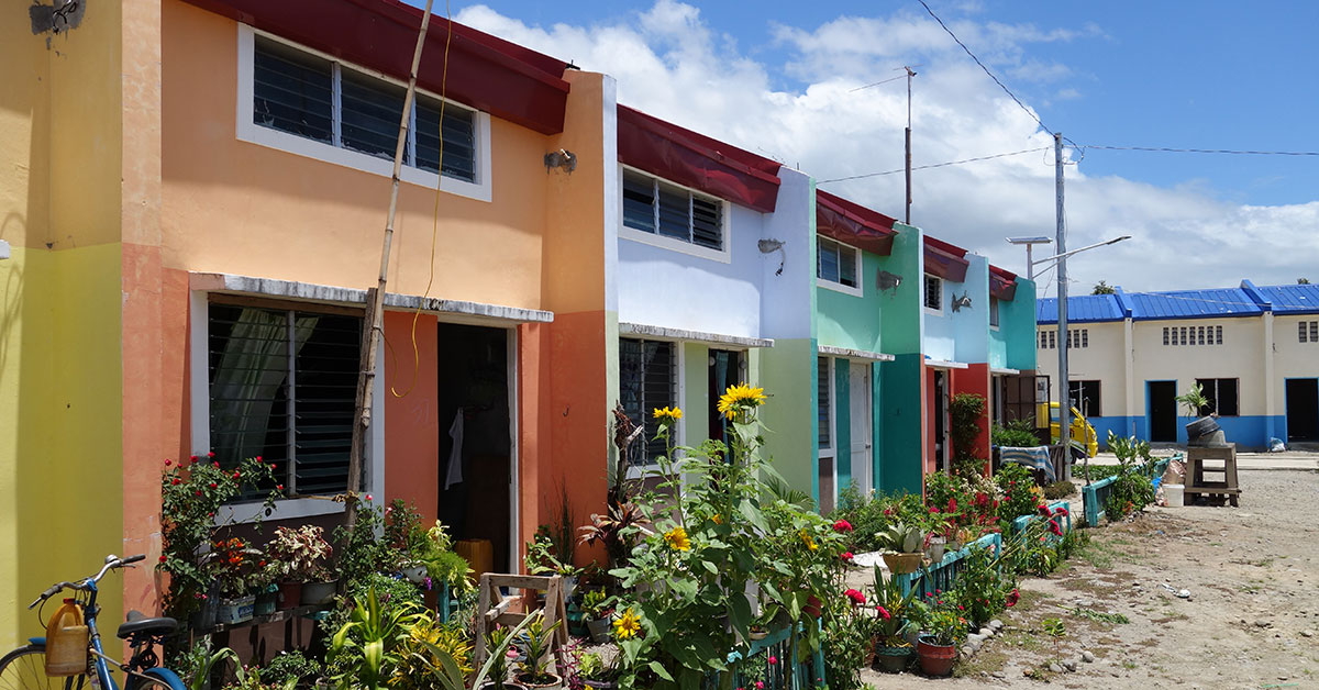 Row of colorful houses with gardens in front
