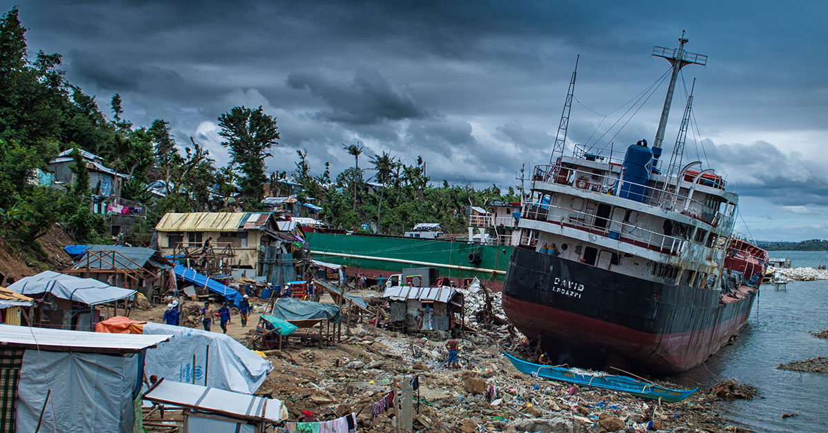 Boat washed ashore next to destroyed houses