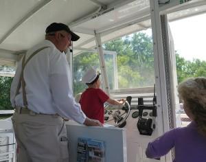 Captain Jerry Gertz gives over the wheel to a young passenger  © 2015 Karen Rubin/news-photos-features.com