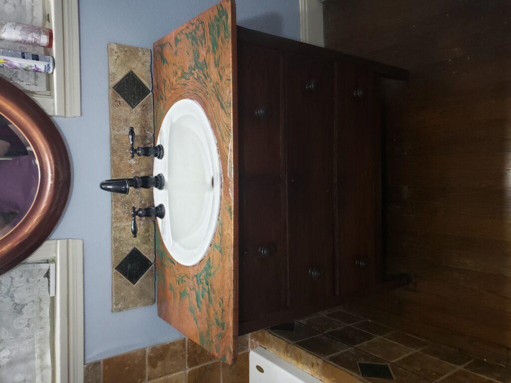 Custom metallic copper and emerald epoxy bathroom sink counter