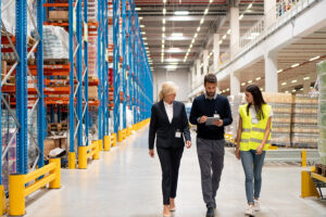 man walking down manufacturing warehouse of factory wih two women and surveying