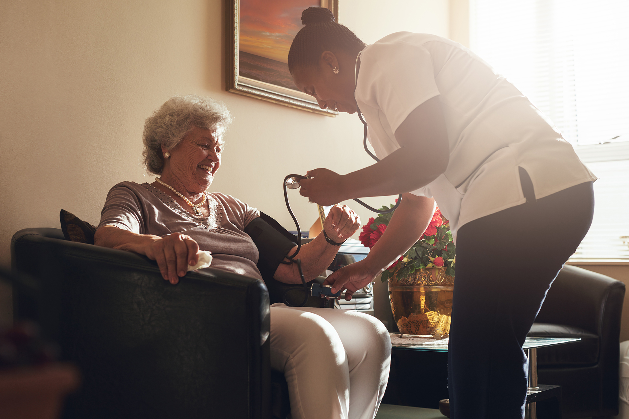 Nurse measuring blood pressure of senior patient in retirement h