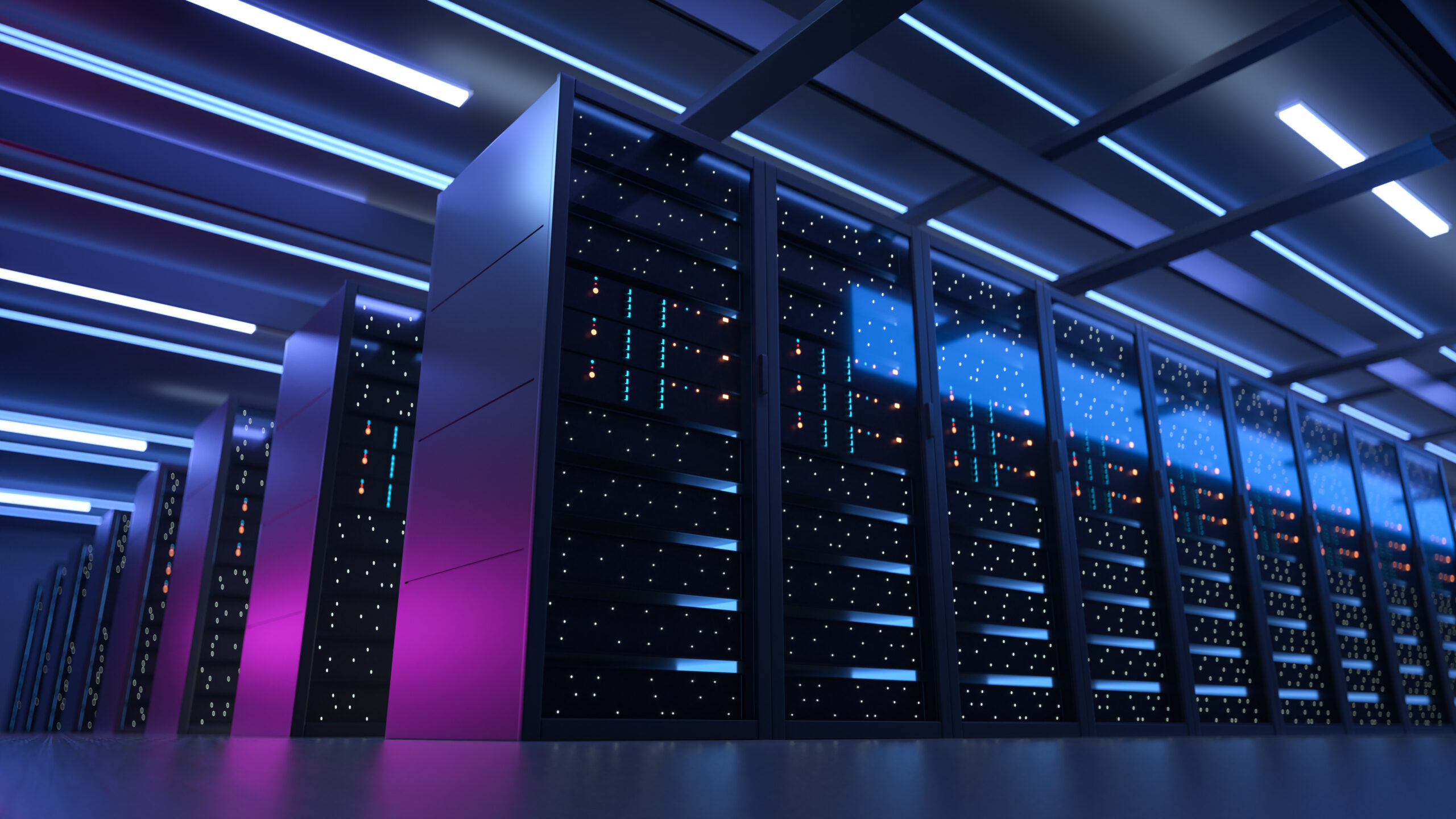 Wide angle shot of rows of server cabinets lined up next to each other in working data center. Led lights on server cabinets. Room illuminated by purple glow from lighting.