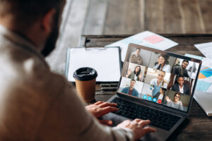 App for communication with employees. Online video conference. Young bearded man communicates via video call with business partners, he sits at the creative modern office space