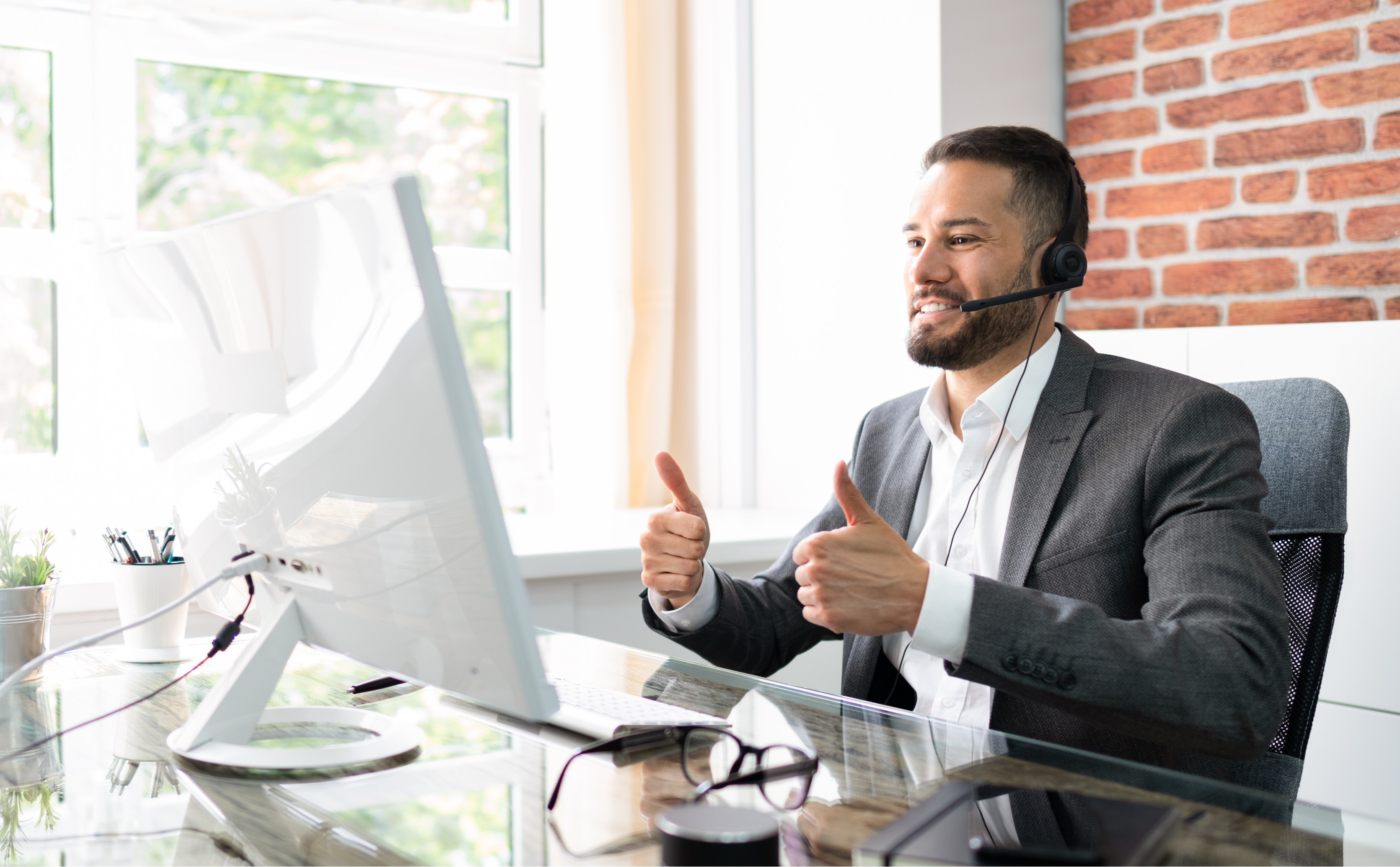 Customer service agent bearded man on video call with client, giving two thumbs up to camera. Business man is smiling and wearing a headset. VOIP connection.