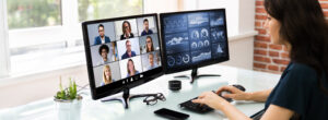 Young woman on online pbx voip video conference with nine other business men and women. Second monitor displays infographics and metrics.