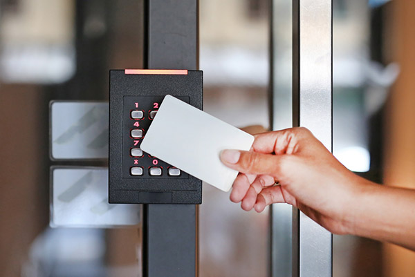 Depiction of keycard being used on number combination keypad to allow entry to door through keycard.