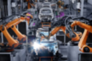 blurred photo of automated machines building a car