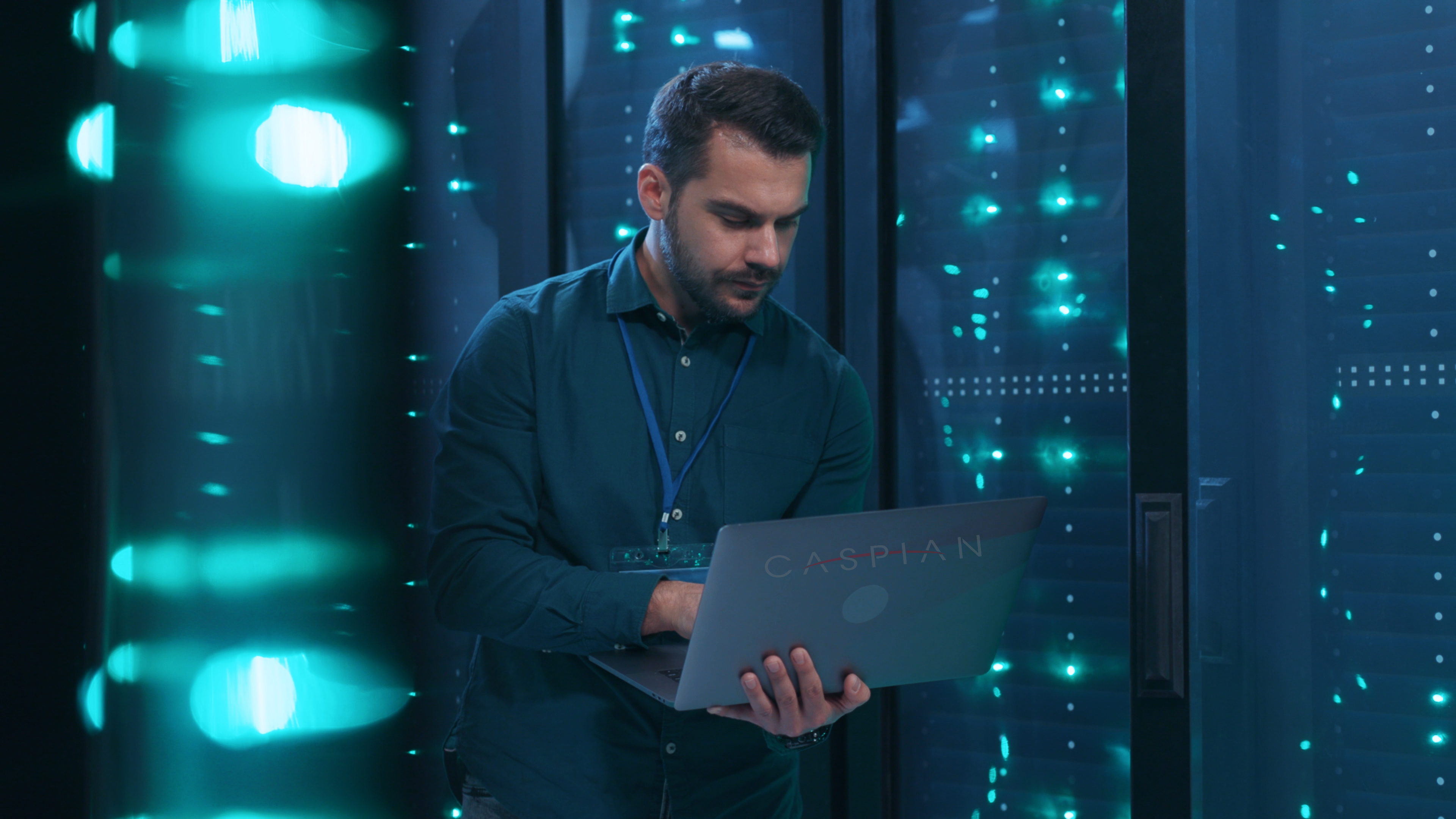 man on laptop with Caspian sticker monitoring server cabinets