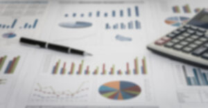 blurry photo of financial charts with pen