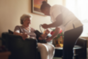 Blurry image of nurse measuring blood pressure of senior woman patient in retirement home. Home caregiver doing routine checkup of a mature female patient.