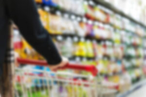 blurred photo of shopping cart being pushed down grocery aisle