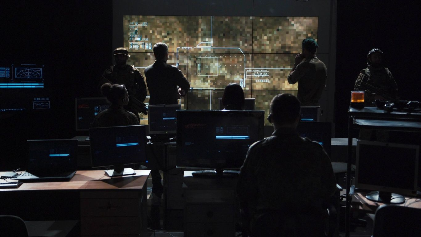 group of people viewing monitors with large overhead display