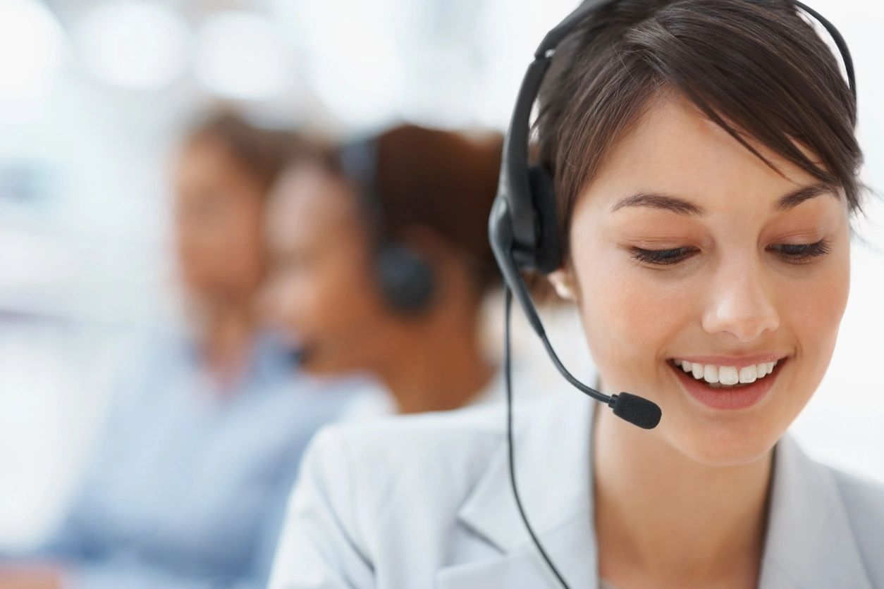 Young woman in call center or service desk smiling and doing work. In background are the silhouettes of two other women are also on calls