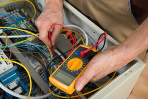 Fluke electrical voltage tester with no reading being used to measure output of wire or cable inside of cabinet.