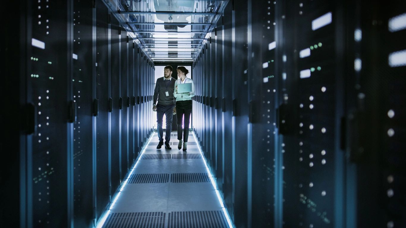 Man and woman walking down hallway in working data center. Floor and server cabinets are illuminated by light. Monitoring data center.