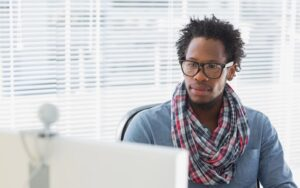 Young trendy man with glasses and scarf on video conference call. Background is window with natural sunlight coming through. Webcam is visible on top of computer monitor.