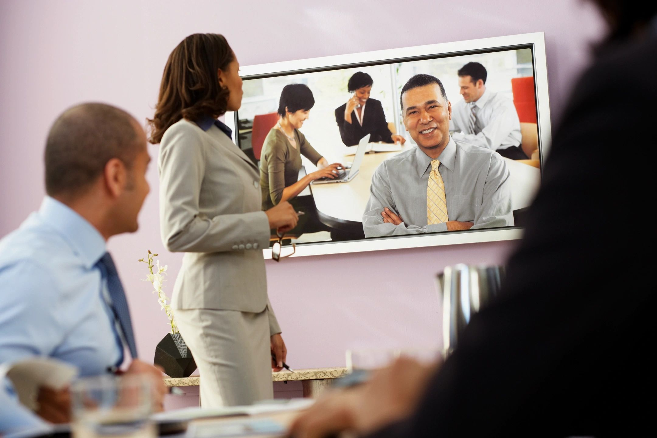 Image of three people on video conference call over the internet having a meeting. Video is displayed on TV. Four business people on opposite end of call smiling.