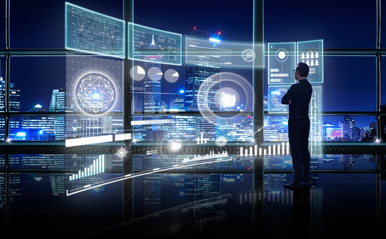 Business man standing in front of window with depiction of graphical communication display in front of him. Outside of window is night sky with illuminated city skyline.