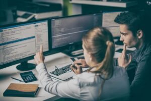 blonde woman helping man at computer pointing to HTML code