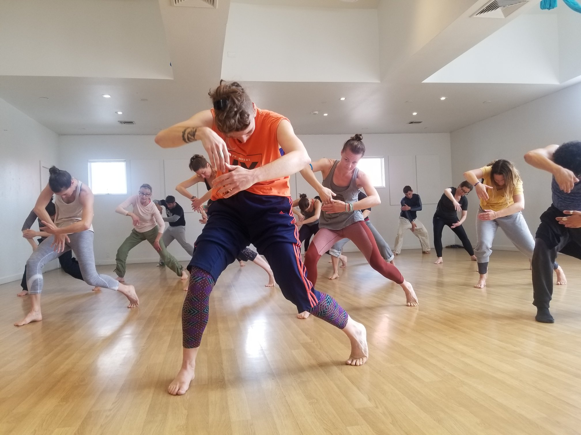 Woman standing in front of large group behind her leading a movement threading her right hand through a space that her left hand has created. The left hand is moving down and this picture captures the moment it is about to meet the right hand, which is extended in front of her chest. The students behind her are mimicking the movement. The teachers is dressed in a bright orange shirt and navy blue exercsie pants with orange pants down the side. Her legs are spread apart and bent with the left heel cocked off the floor; her body is in a slight contraction forward and her focus is down.