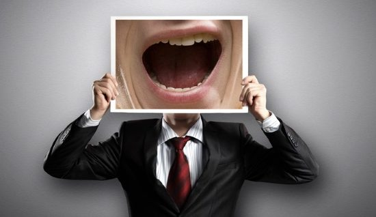 A businessman holding up an oversize image of an open mouth in front of his face