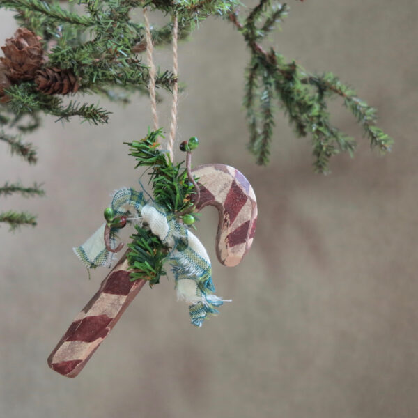 red and white candy cane ornament with green bow and pine