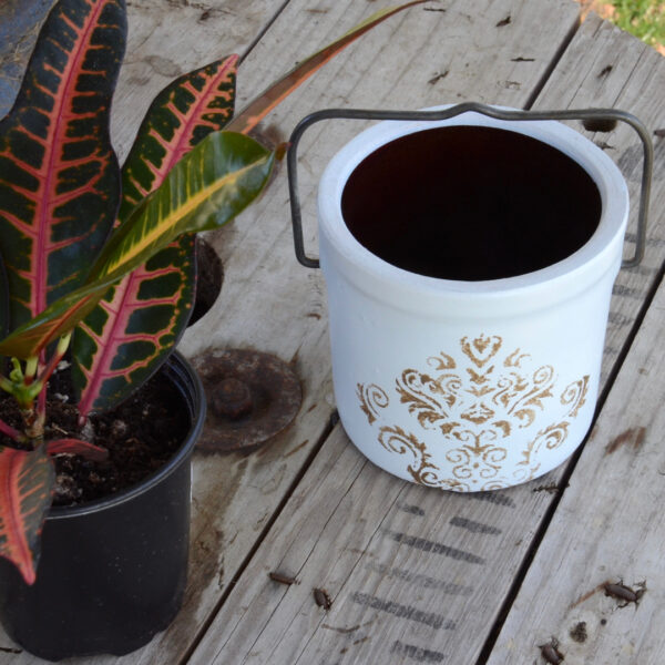 butter crock repurposed into a planter painted white with metallic decorative stencil and original metal handle picture next to a plant