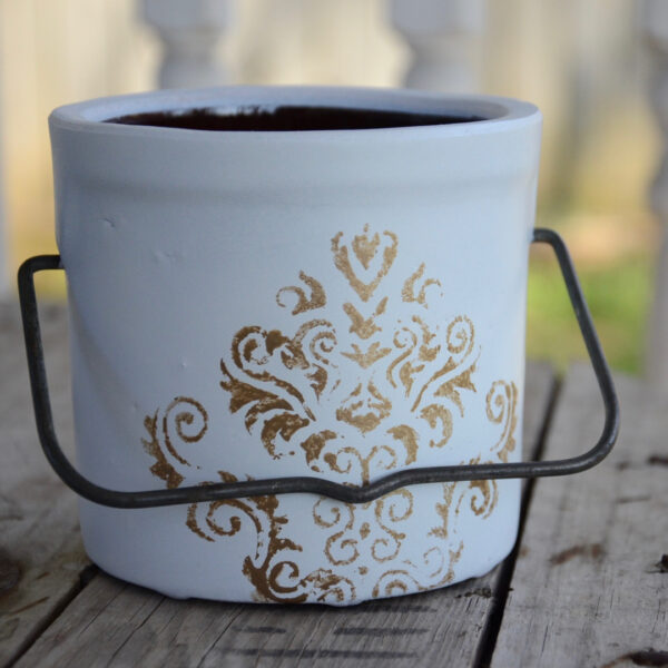butter crock repurposed into a planter painted white with metallic decorative stencil and original metal handle