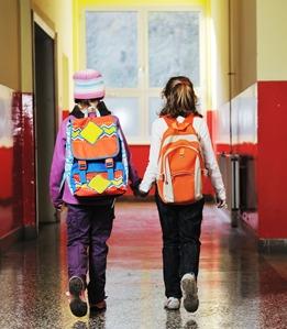 Happy two girls walking indoor at school hall