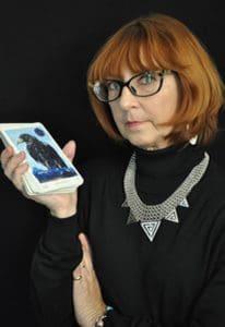 Marcia O'Hara in a black turtleneck holding image of Awakening Aeon Tarot Deck