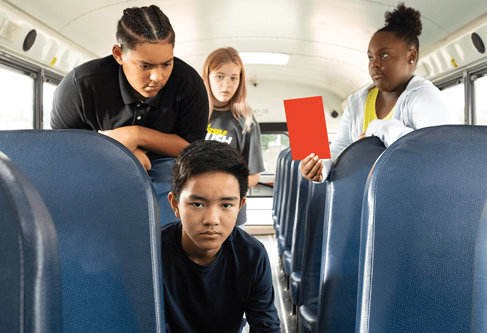 A student is being bullied on a school bus and another girl is pulling a Red Card to stop the bullying.