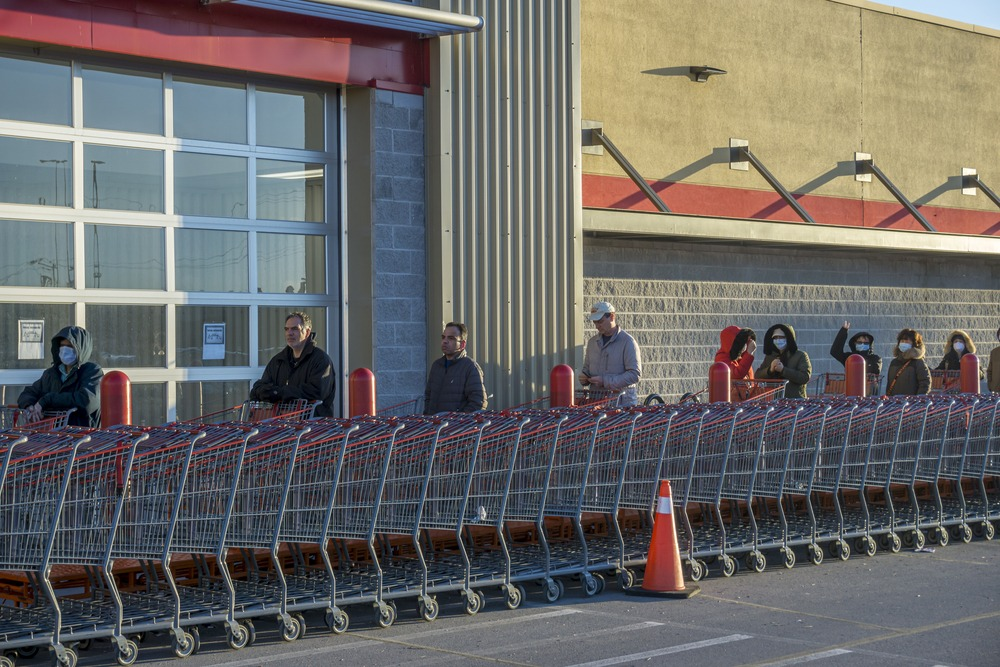 Toronto, Canada, April 2020 - Customers line up by a grocery store respecting the physical distance required by the cover-19 pandemic