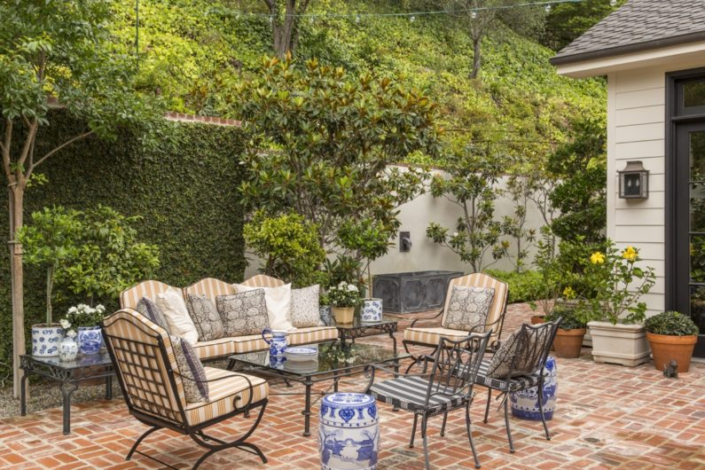 Exterior brick patio with iron frame chairs, sofa and table with glass top, patterned upholstered pillows, ivy climbing back wall, various plastered and potted trees and shrubs, grey metal fountain on far wall.