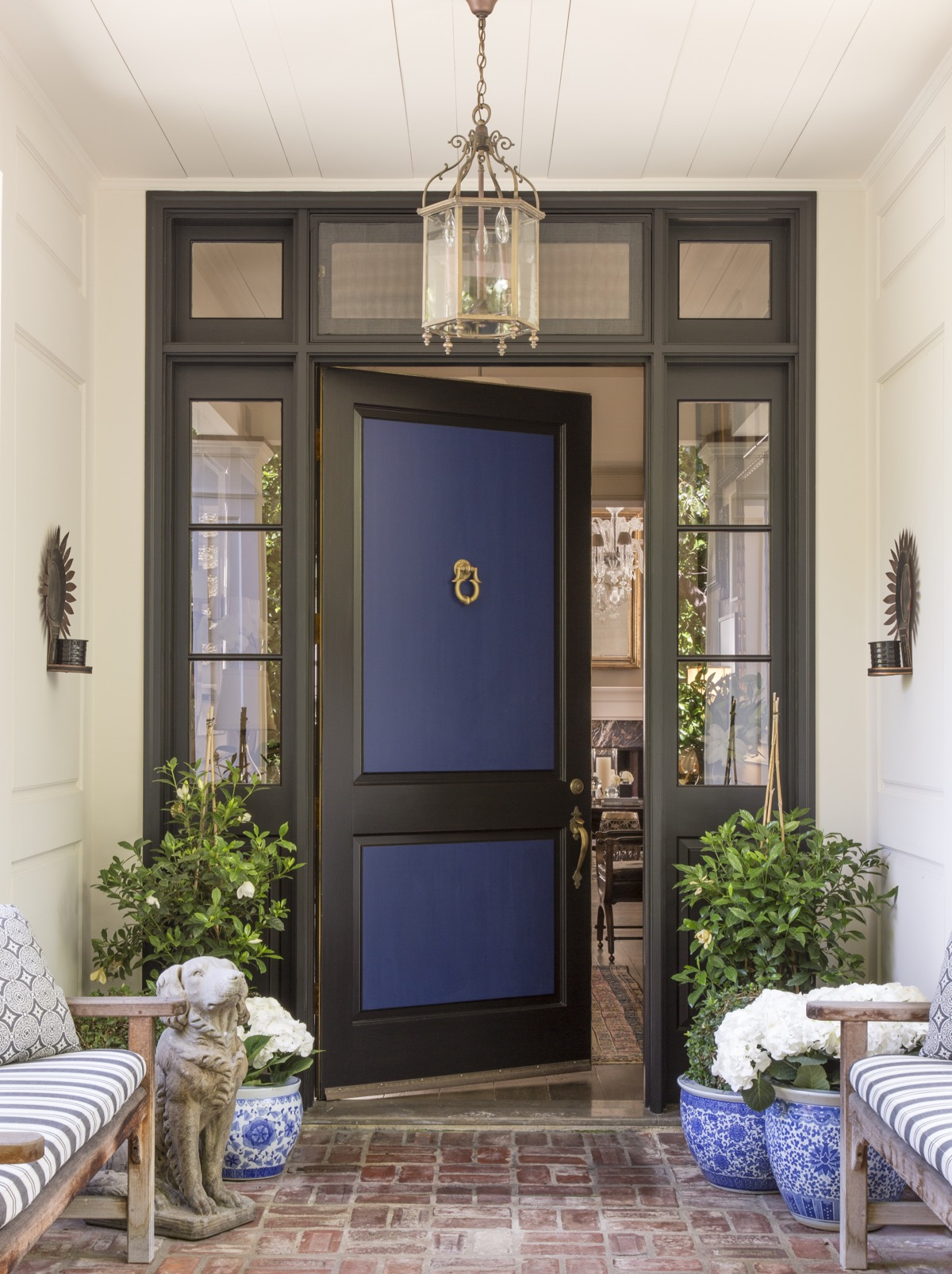Front door overhang with blue door, matching benches with patterned cushions, potted plants.brick walkway.