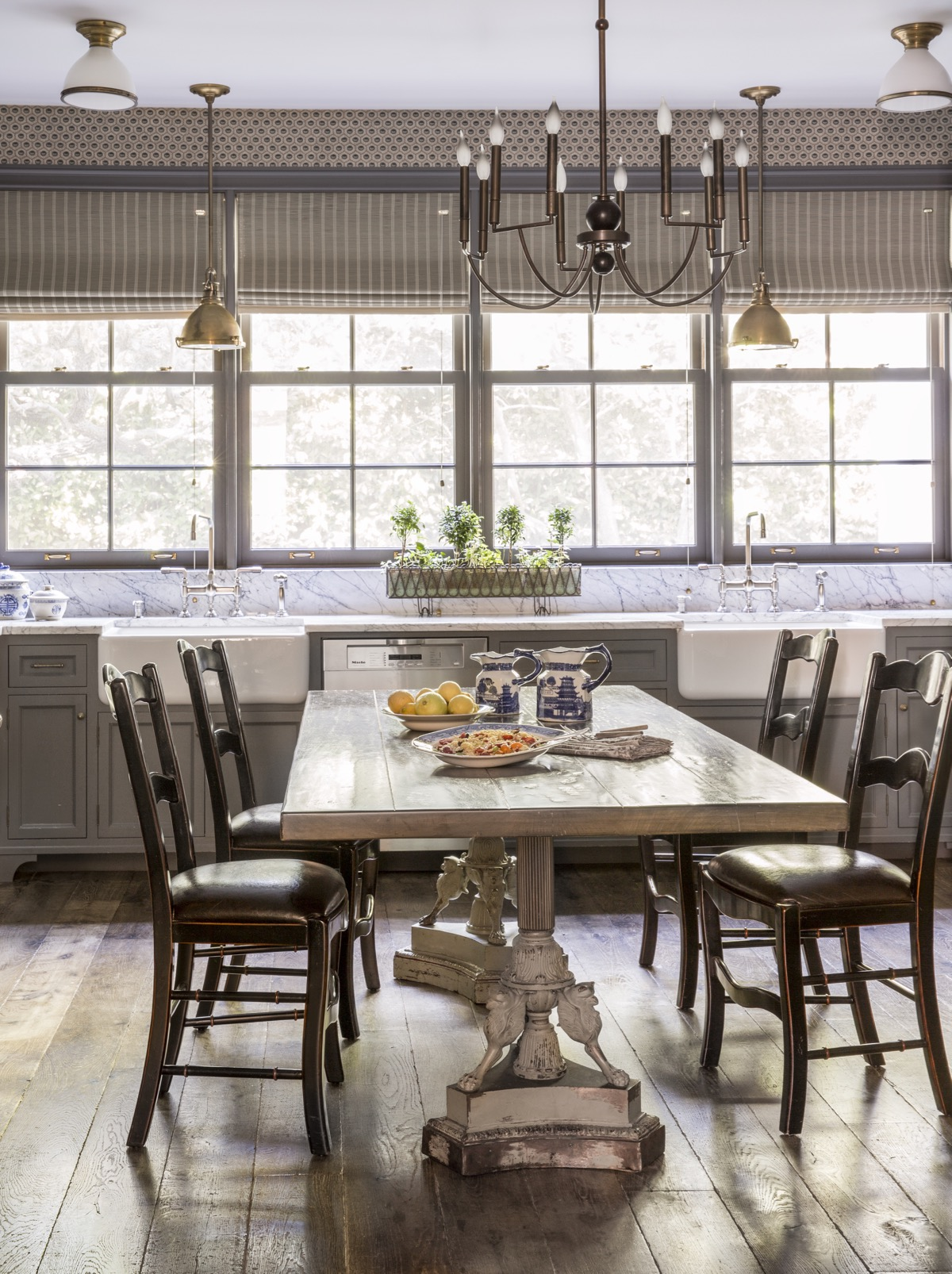 Lage kitchen with wood dining table, hardwood floors, stone countertops, and large windows looking out to green yard..