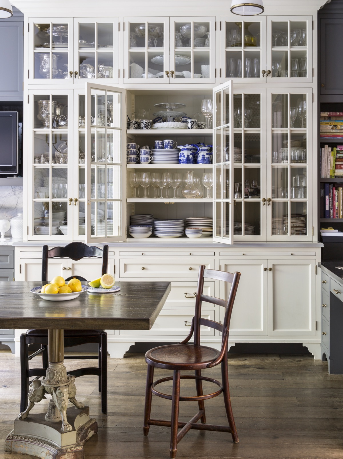 Kitchen with floor to ceiling white wood cabinets with various glasses, dishes, etc.