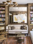 Library with built in loveseat, wall mirror and floor to ceiling shelves with various books.