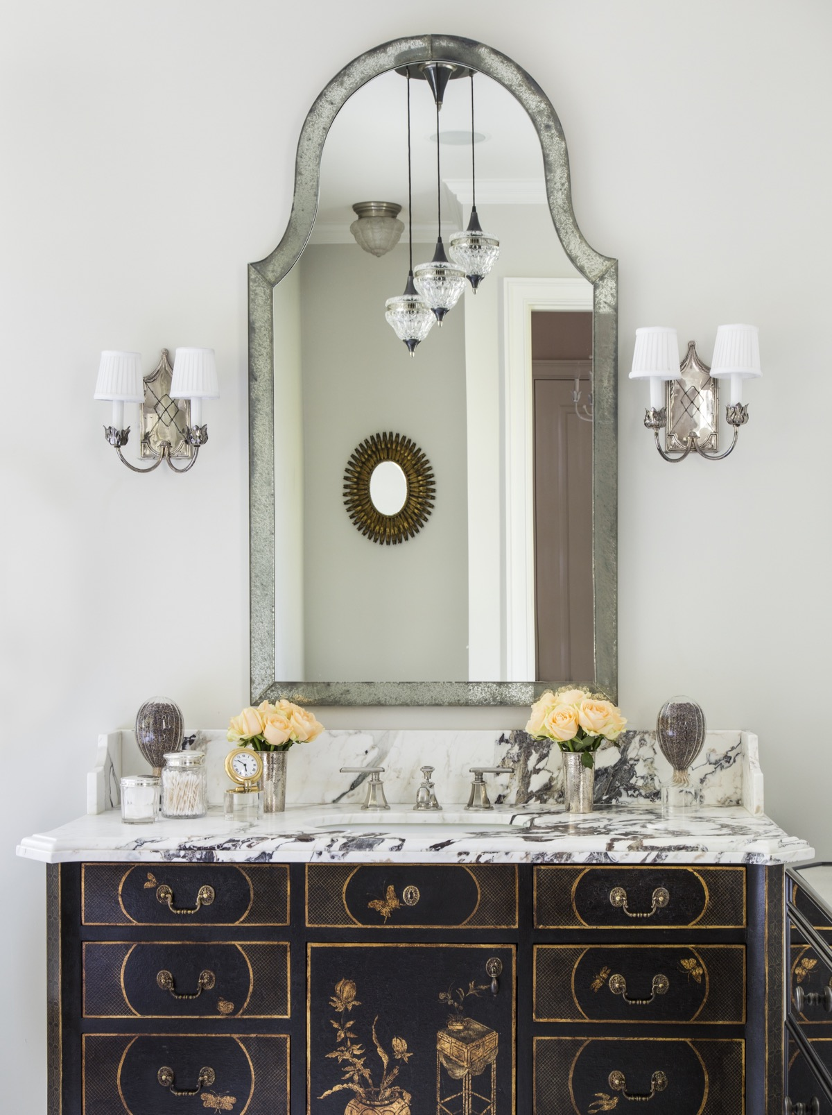 Detail of bathroom vanity with antique finish, stone top, various containers, flowers on countertop.