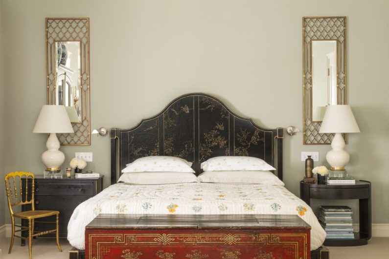 Master bedroom with large bed with leather textured headboard. Matching side tables, with lamps.