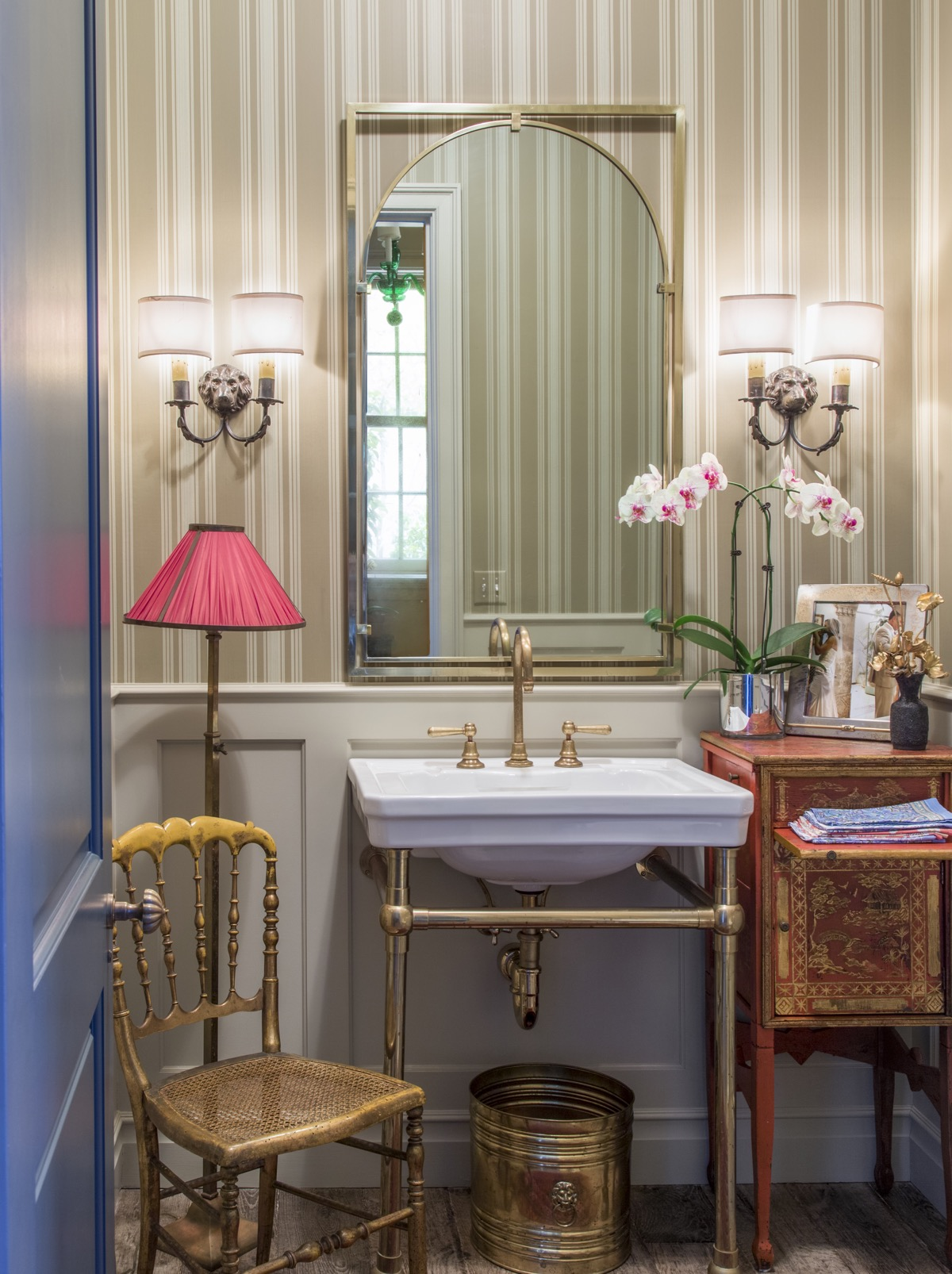 Powder bathroom with striped vertical wallpaper, ceramic basin with metal framework, matching wall sconces.