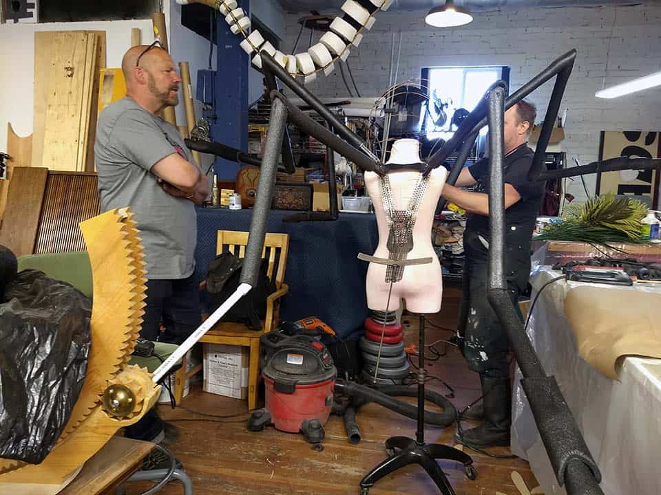 Crit Killen and Hraefn Wulfson with the welded steel shoulder frame and chassis for new custom mosquito mascot on a dress dummy the same size as performer