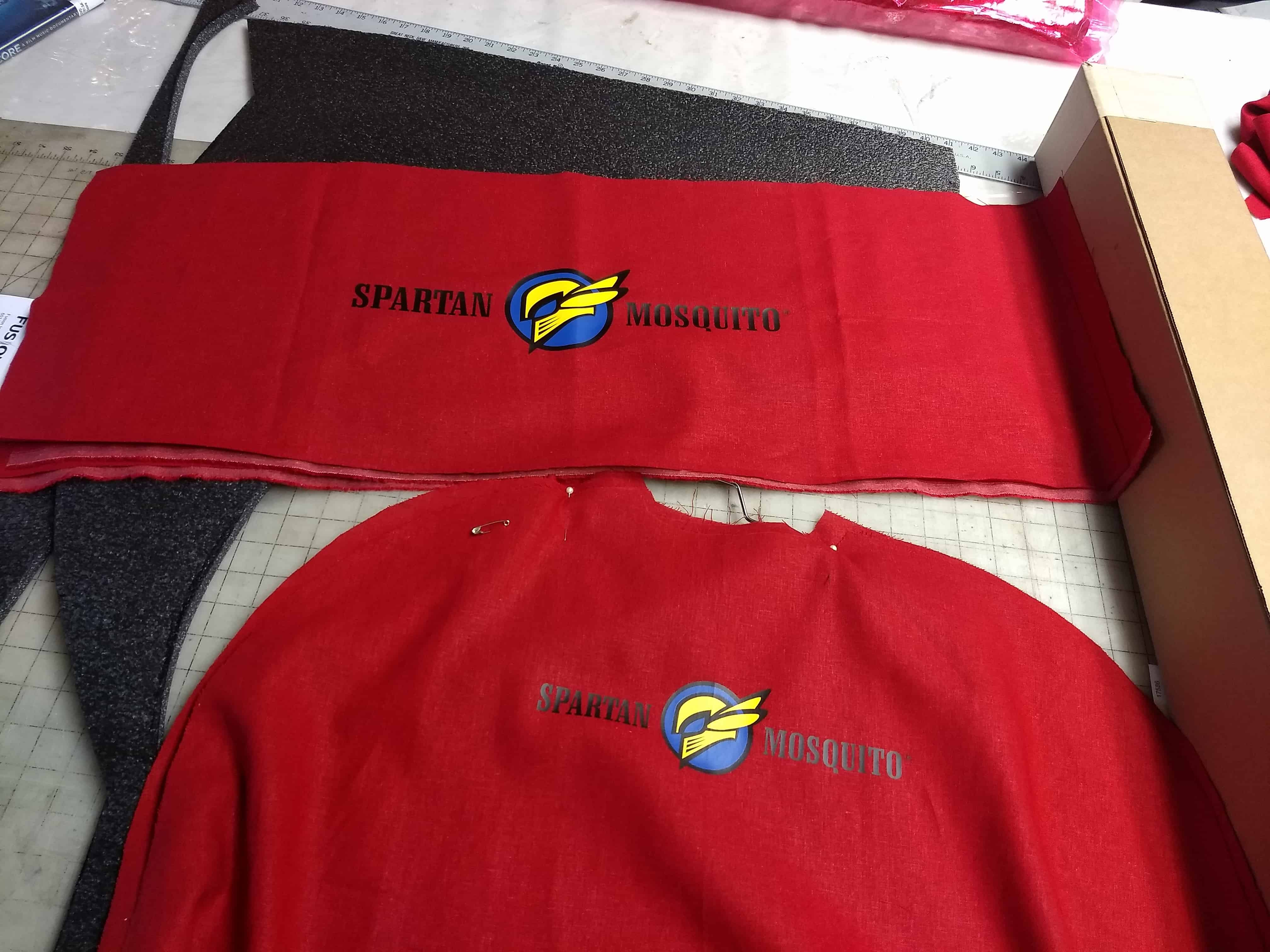 Detail: Spartan Mosquito logo heat transfers on Spartan cape backs and wagon banners