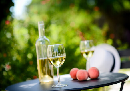 2-glasses-white-wine-on table-with-peaches