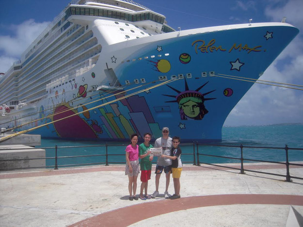 """In July, Liz, John, Michael & Matthew Urbano enjoyed an extended family reunion cruise to Bermuda for 7-nights aboard the Norwegian Breakaway.  This new ship had lots of fun activities including a ropes course, rock climbing wall, five full-size water slides including twin """"free fall"""" slides, and miniature golf.  While in Bermuda, we went swimming and snorkeling at Warwick Long Bay Beach and Horseshoe Bay Beach, both located in the South Shore Park.  Pictured (l-r): Liz, Michael, John, and Matthew Urbano in front of the Norwegian Breakaway docked in Bermuda at Kings Wharf, Royal Naval Dockyard."""