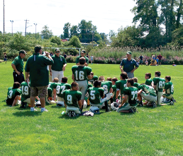 The 5th/6th grade Nashoba Youth Football team during halftime at Saturday's. jamboree. Head coach Mike Guthrie speaks to the team.            Michael LeClair