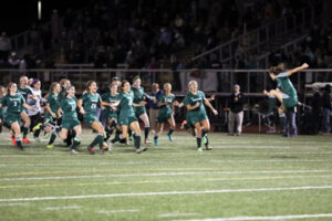 Nashoba Girls Soccer capped off a winning week by defeating Wachusett Regional to earn the  District 1 Championship Title for the third time in five years. The score remained tied at 0-0 after two sessions of overtime, when Nashoba's Grace Keith hit on penalty kicks, winning the game 1-0. Pictured above, Keith is seen jumping for joy (right) just after the winning kick, as her teammates runs out to celebrate their victory. More on the story below.                                             SusanShaye.com